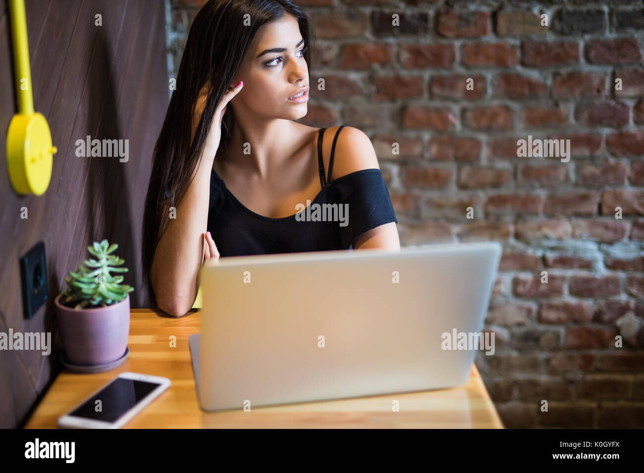 Beautiful Caucasian woman dreaming about something while sitting with portable net-book in modern cafe bar, young charming female freelancer thinking  - Stock Image