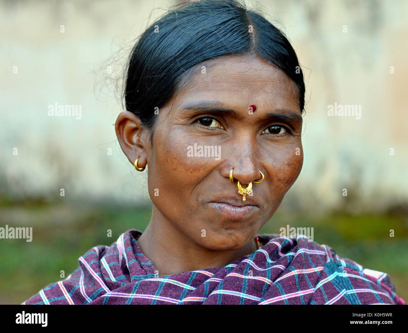 Mature Indian Adivasi market woman with three golden nose rings, nose jewellery, distinctive tribal earrings, and - Stock Image
