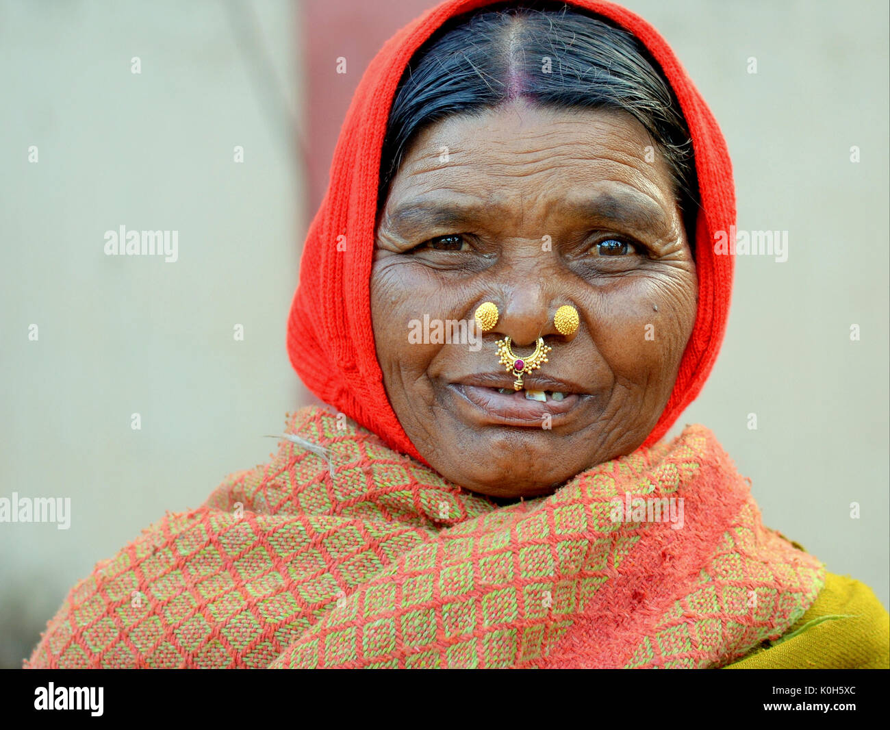 Elderly Indian Adivasi market woman with two golden nose studs and distinctive gold-and-gemstone nose jewellery, - Stock Image
