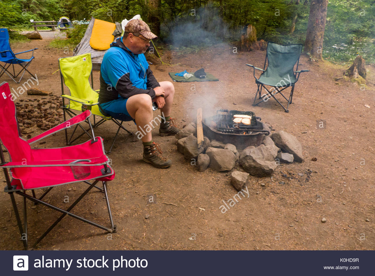 Man Sitting On Folding Camp Chair In The Riverside Campground Watching Camp  Fire, Willamette National