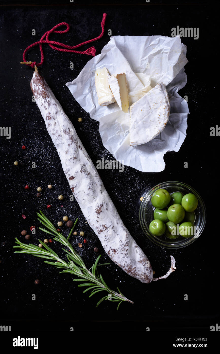 Fuet sausage with cheese and olives. Spanish snack on black background. Top view. - Stock Image