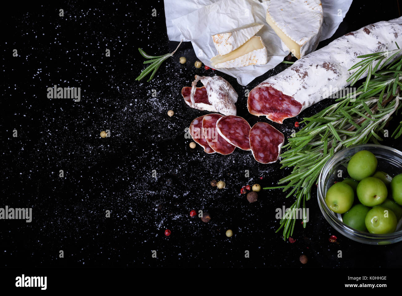 Salami, smoked sausage, olives and rosemary. Traditional spanish fuet snack. Above view, white background. - Stock Image