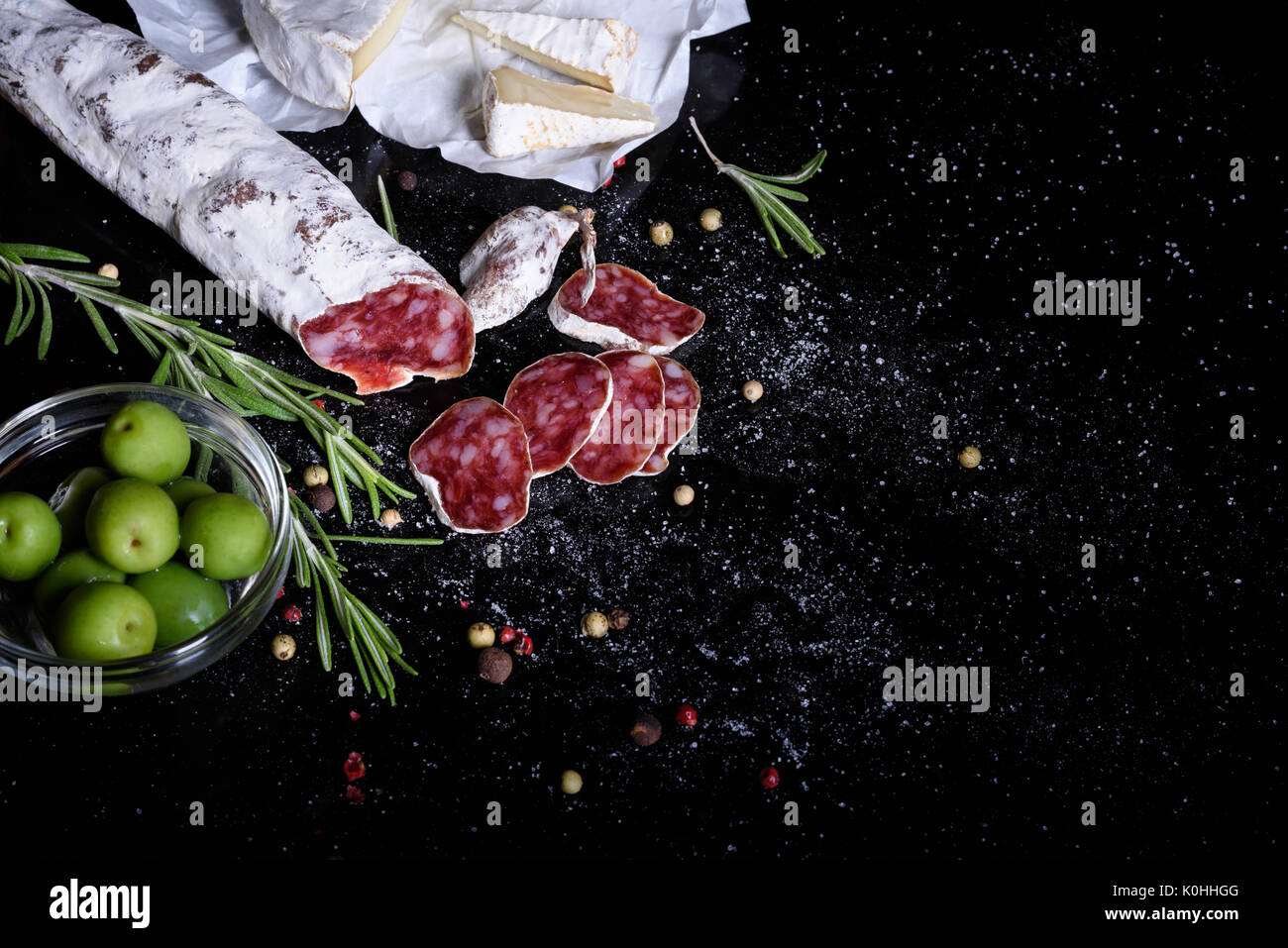 Traditional spanish snack on black background. Fuet sausage with cheese and olives. Top view. - Stock Image