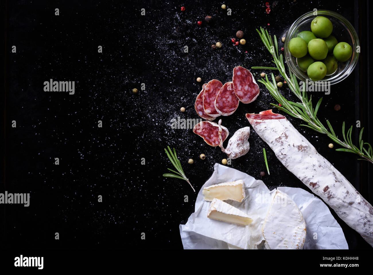 Cured Fuet cut into slices with cheese and olives. Salami sausage snack. Copy space, above view, dark background. - Stock Image