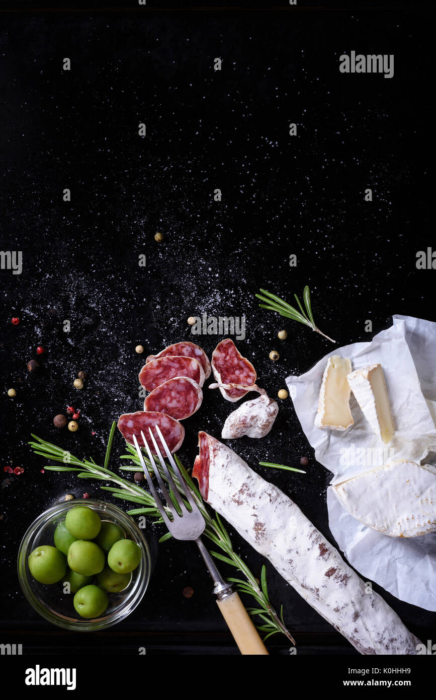 Traditional spanish snack fuet salami sausage with cheese and olives. Top view. - Stock Image