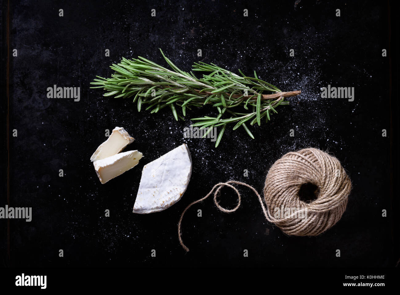 Brie cheese with fresh herbs, swiss appetizer. Top view. - Stock Image