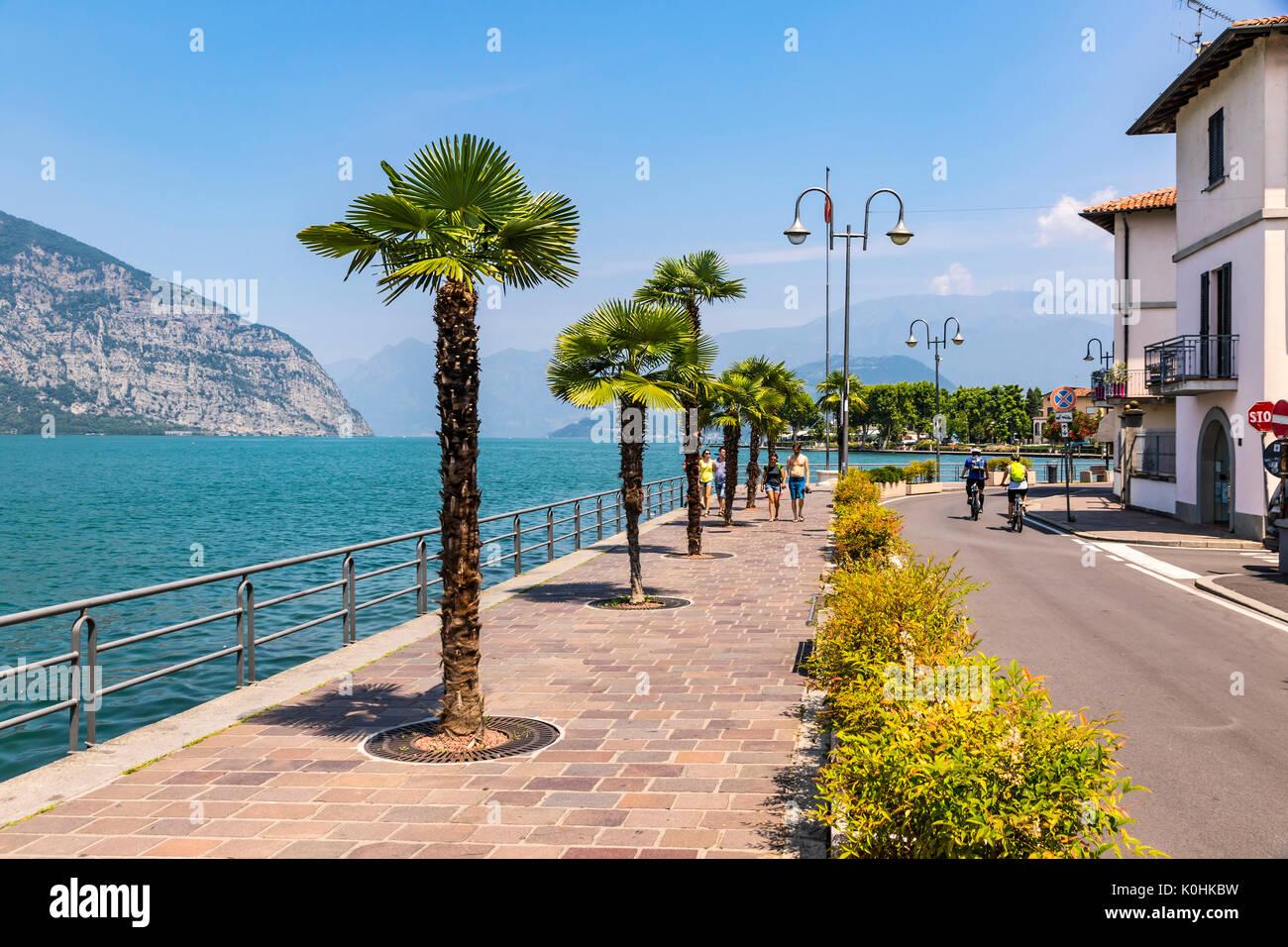 ISEO, ITALY - JUNE 17, 2017: People walking on Promenade street in Iseo city on Iseo lake, Lombardy, Italy. Famous Italian resort. Lake Iseo (or Lago  - Stock Image