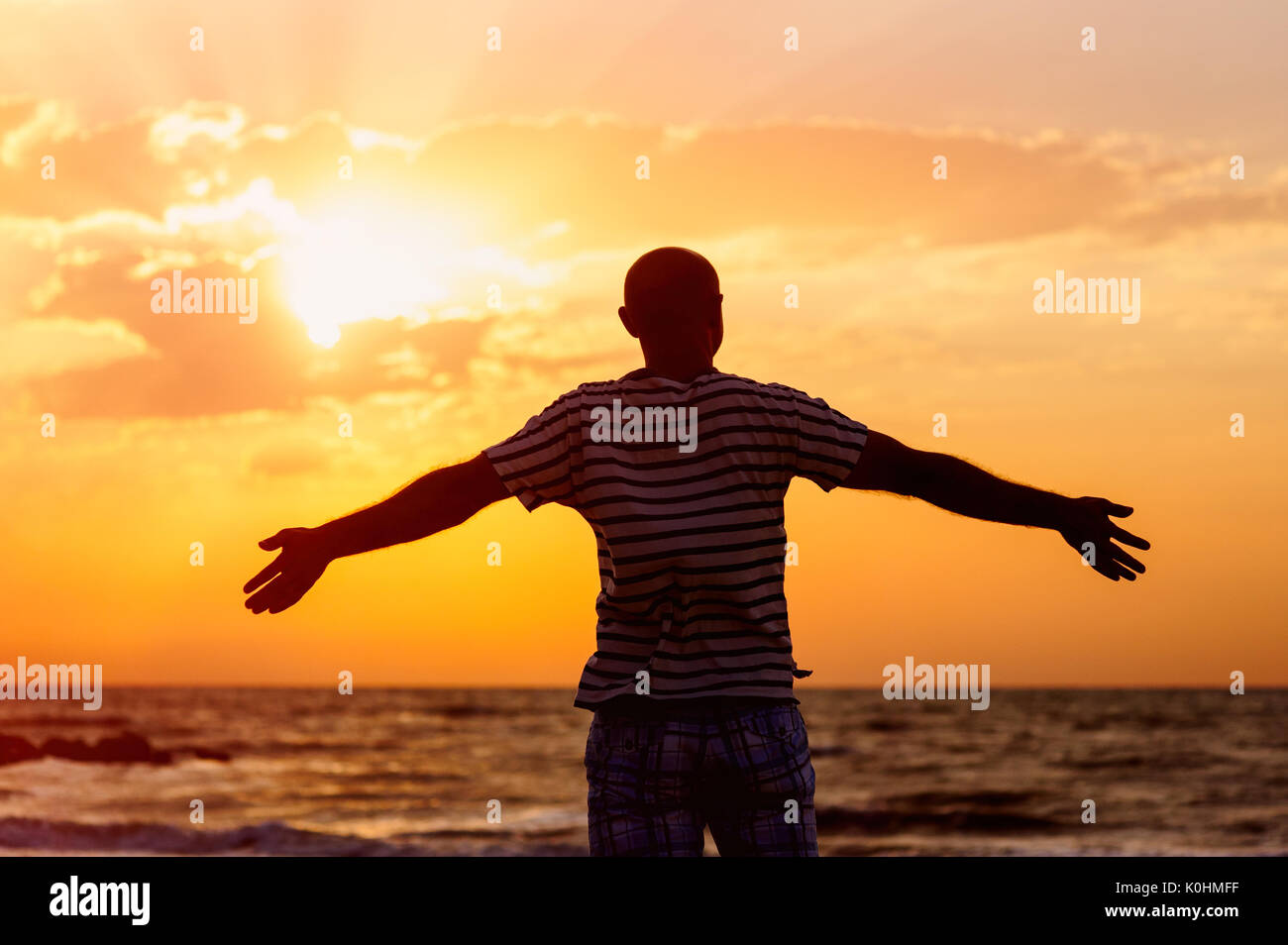 Happy man raises his arms up against the sea Stock Photo