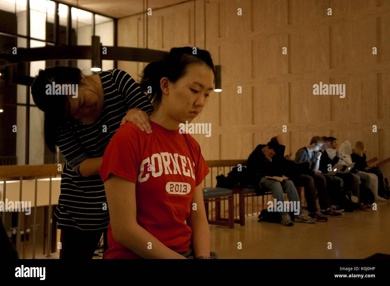 A member of the Stress Busters, a student group that gives free massages to their peers, gives one of her peers a back massage as other students wait on a bench, studying, on Q-Level of the Milton S. Eisenhower library on the Homewood campus of the Johns Hopkins University in Baltimore, Maryland, 2015. Courtesy Eric Chen. - Stock Image