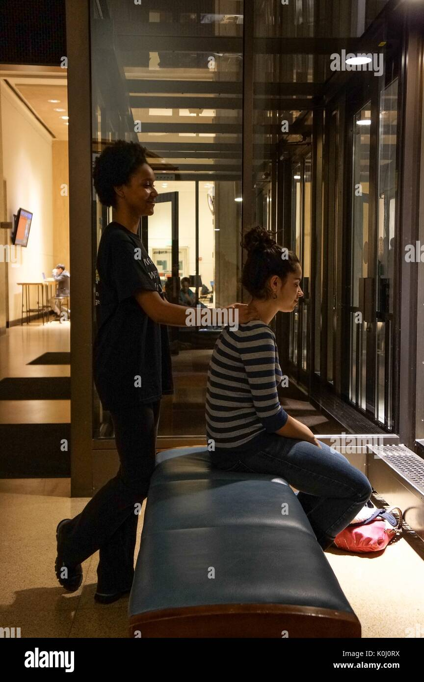 A member of the Stress Busters, a student group that gives free massages to their peers, gives a college student a back massage on Q-Level of the Milton S. Eisenhower library on the Homewood campus of the Johns Hopkins University in Baltimore, Maryland, 2015. Courtesy Eric Chen. - Stock Image
