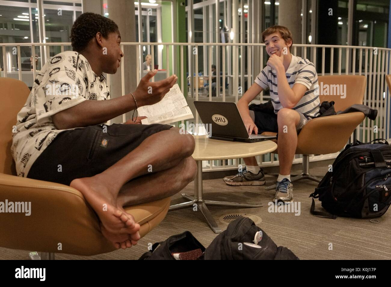 Two male students sitting on chairs of the first floor, Q level, of the Brody Learning Commons, surrounded by study materials, conversing, with smiling facial expressions, 2016. Courtesy Eric Chen. - Stock Image