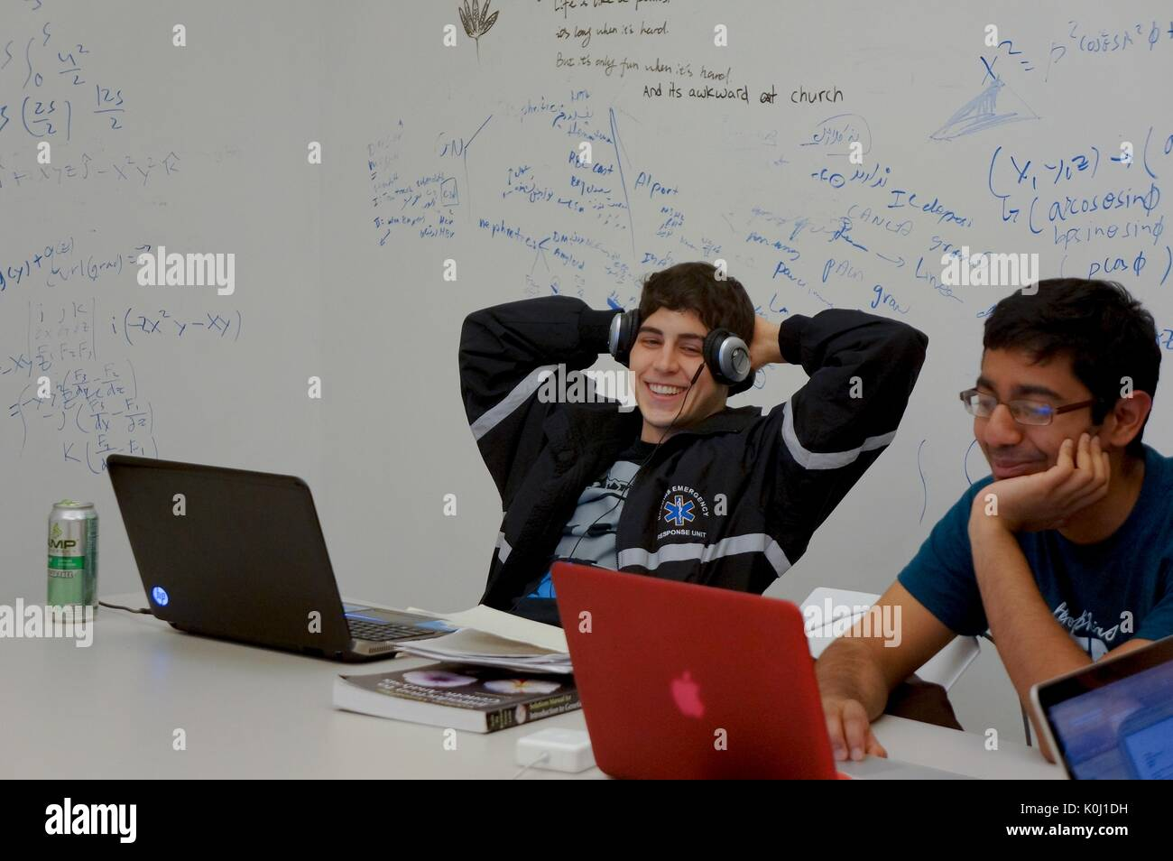 Two male students sitting at a white table with two laptops, study materials, and a canned energy drink; whiteboard walls containing writing and equations in both blue and black marker, smiling facial expressions, 2016. Courtesy Eric Chen. - Stock Image