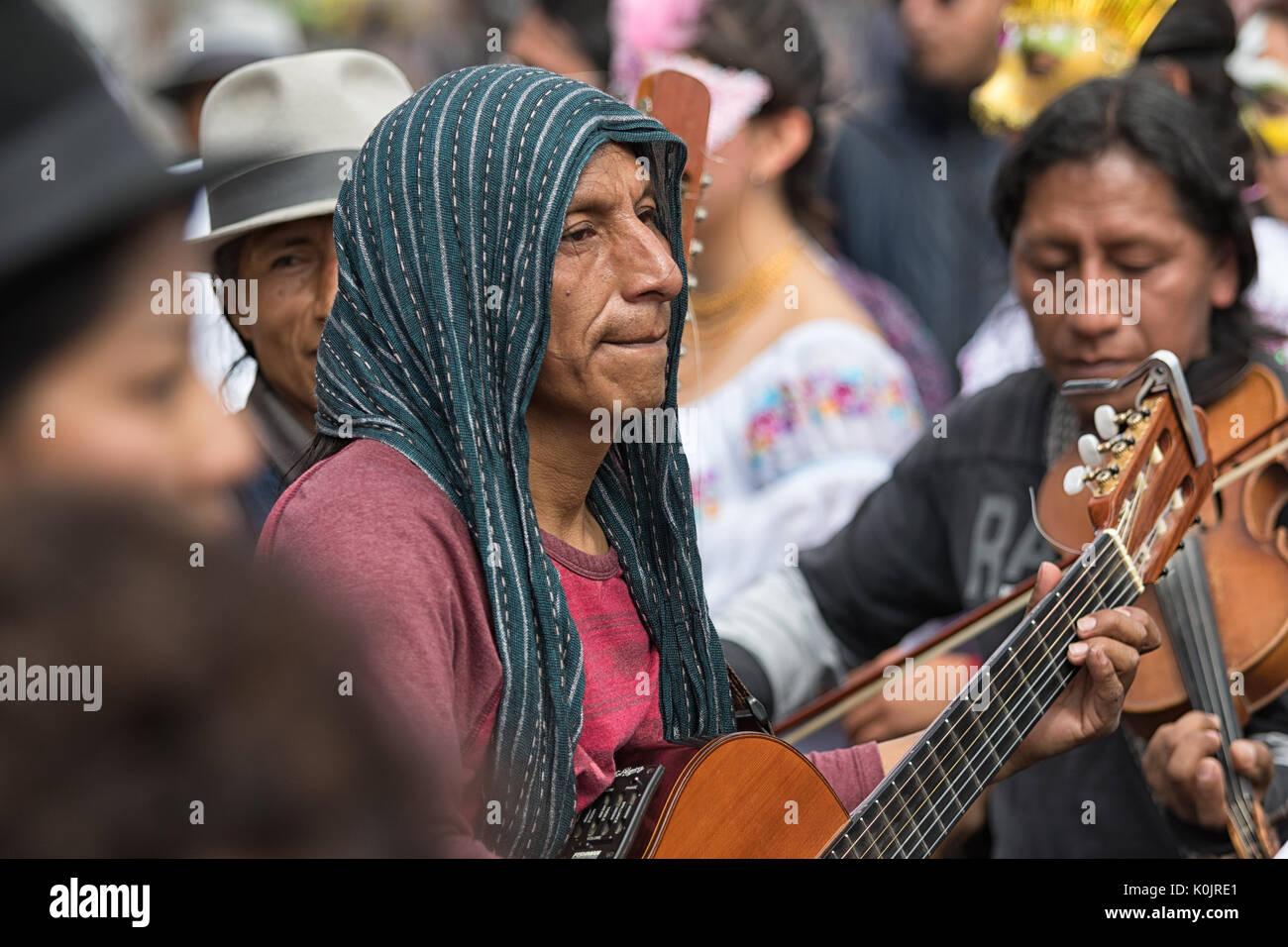 July 1, 2017 Cotacachi, Ecuador: an indigenous Kichwa man playing the guitar during Punchi Warmi celebration - Stock Image