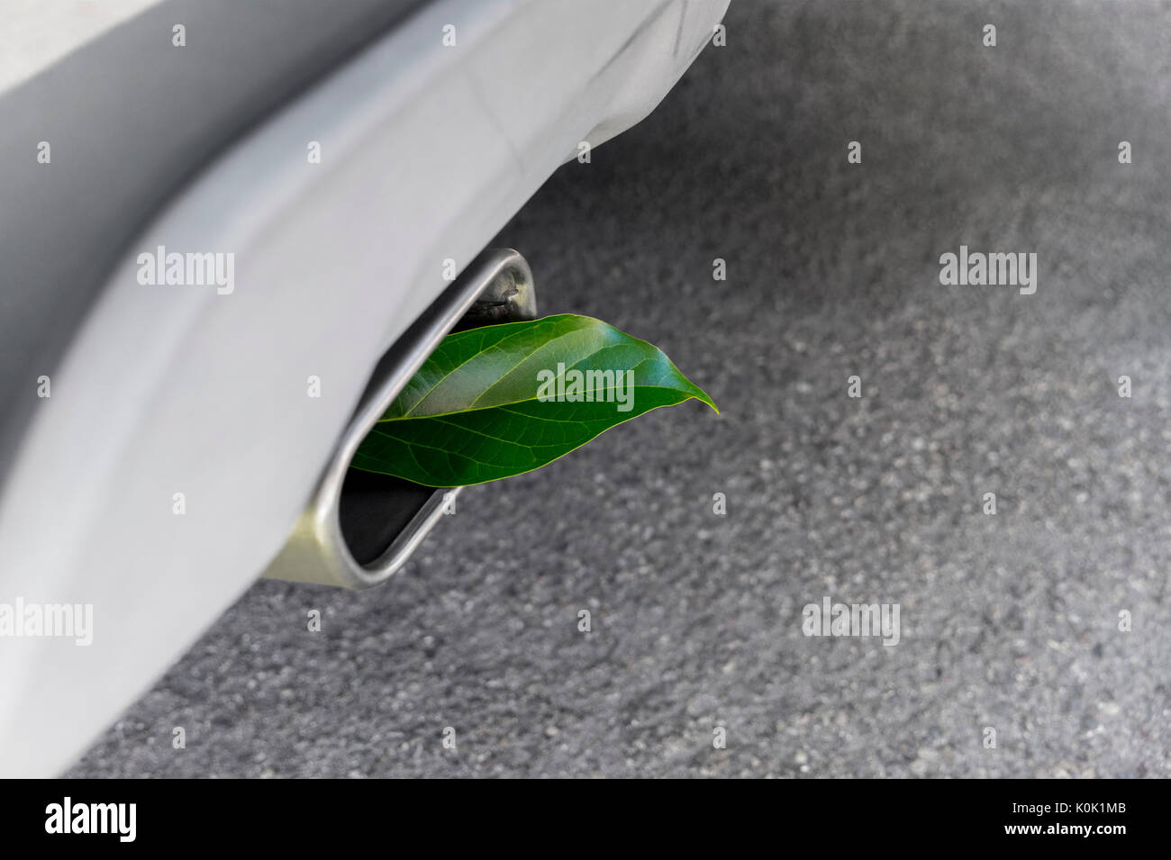 Vehicle greenhouse gas emissions. Fuel efficient car muffler with a green leaf - Stock Image