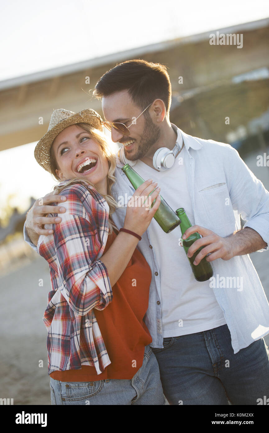 Happy couple smiling and drinking beer at beach Stock Photo