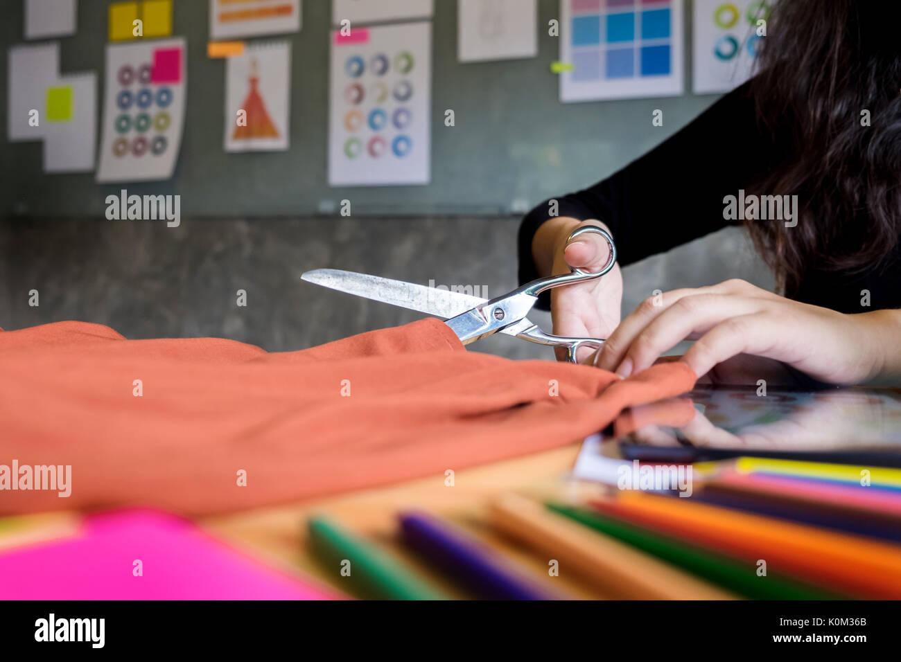 Hands notch tailor tailor's scissors cloth cutting a piece of fabric (fashion designer concept) Stock Photo