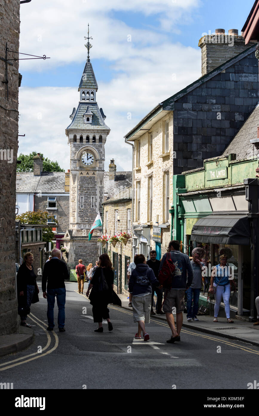 Visitors amble along a street with the town clock in the background at Hay on Wye, a small town on the border of England and Wales. - Stock Image