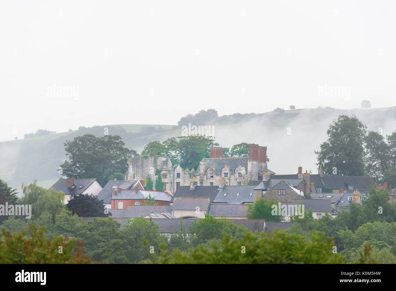 Morning mist surrounds the abandoned castle and houses at Hay on Wye, a small town on the border of England and Wales. - Stock Image