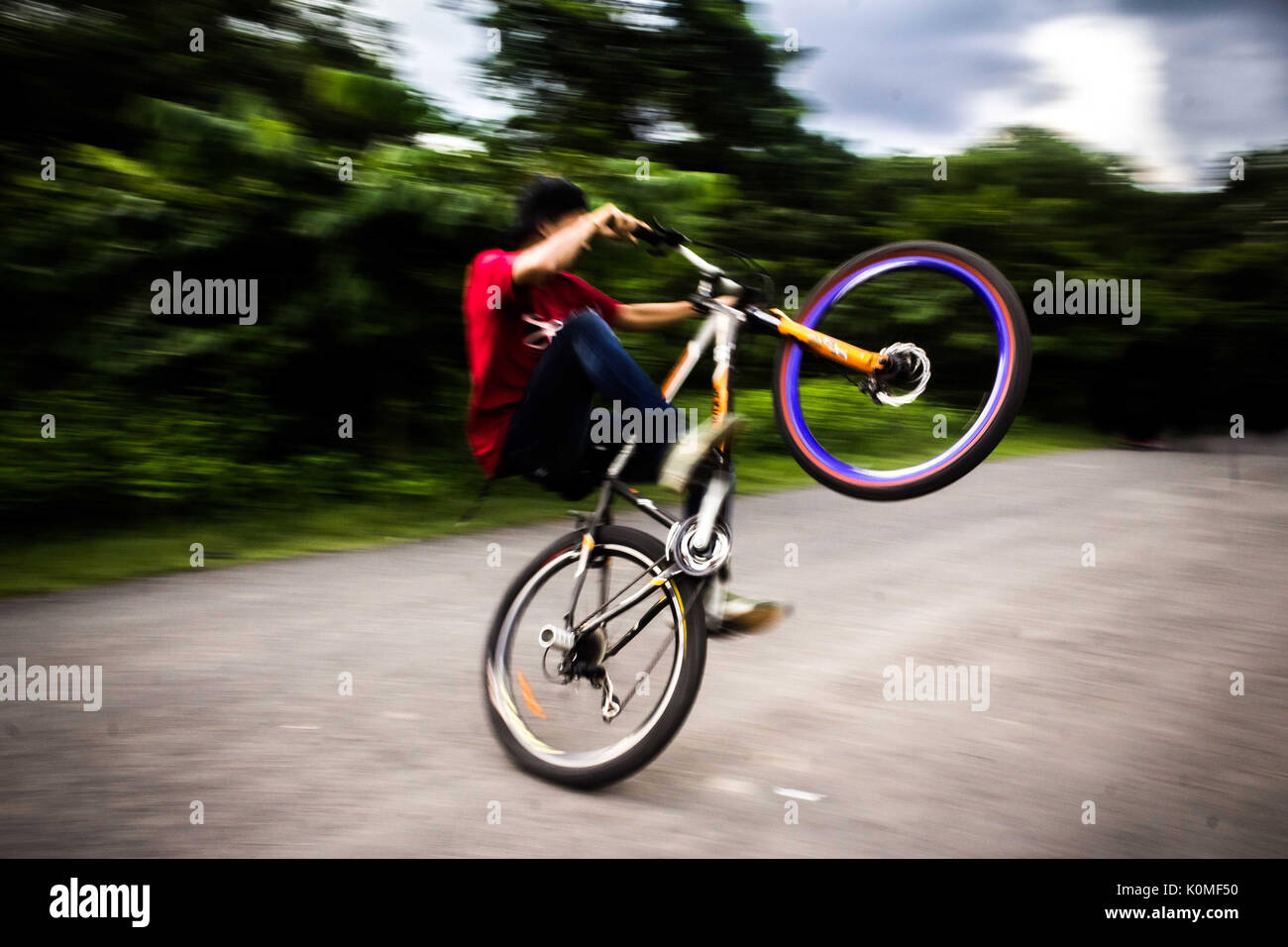 young boy doing by cycle stunts, kolkata, west Bengal, India, Asia - Stock Image