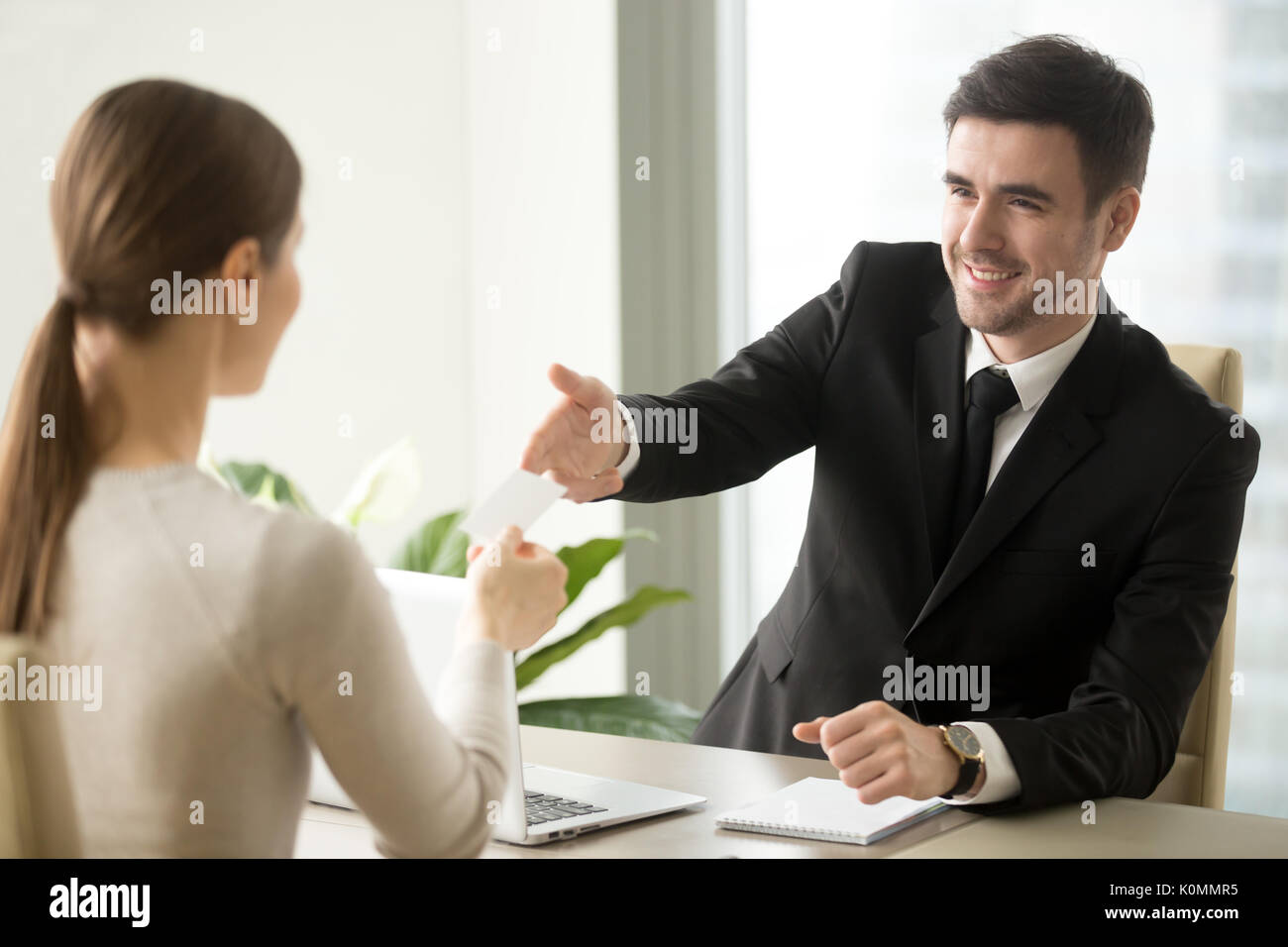 Businessman giving visiting business card to businesswoman at of - Stock Image