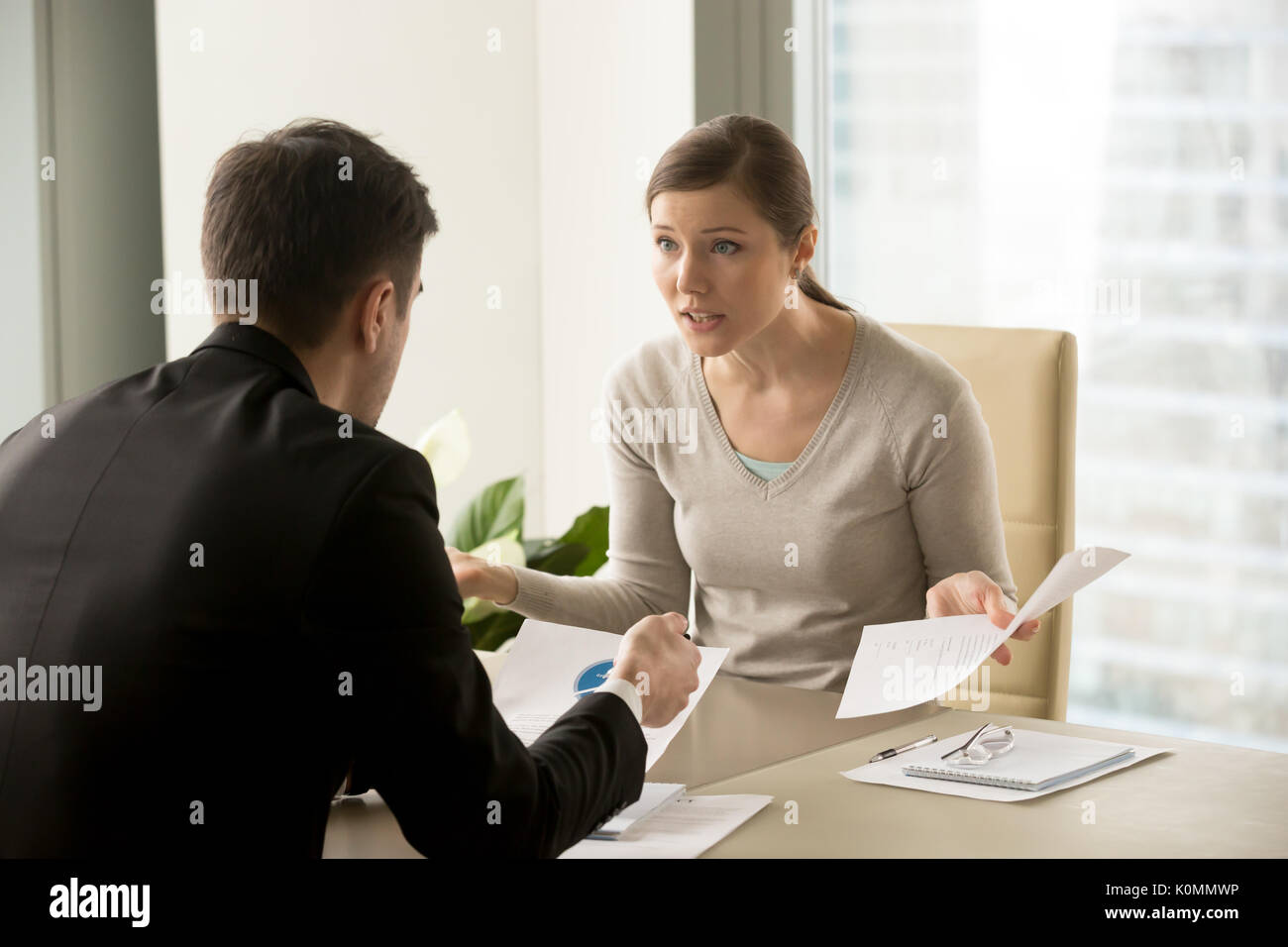 Angry businesswoman arguing with businessman about paperwork fai - Stock Image