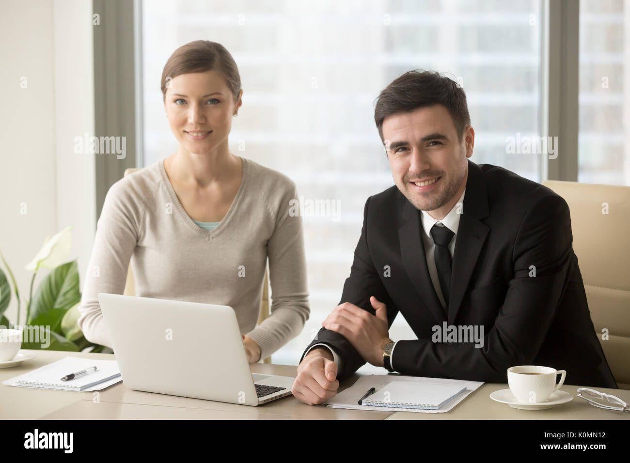 Smiling businessman and businesswoman looking at camera, busines - Stock Image