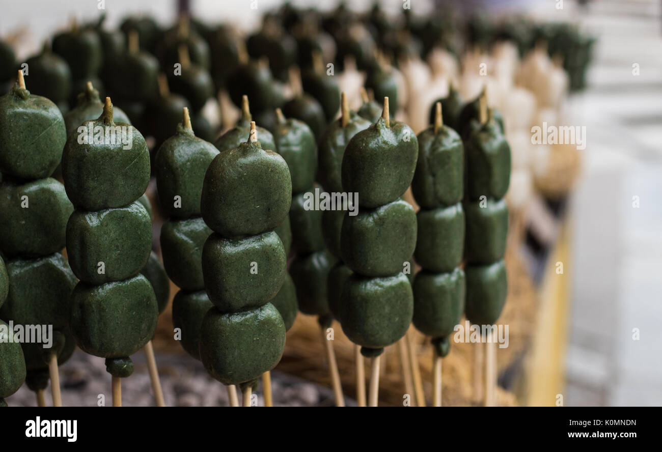 Street food on sale outside a temple in Kyoto, Japan - matcha tea flavour lollies on sticks - Stock Image