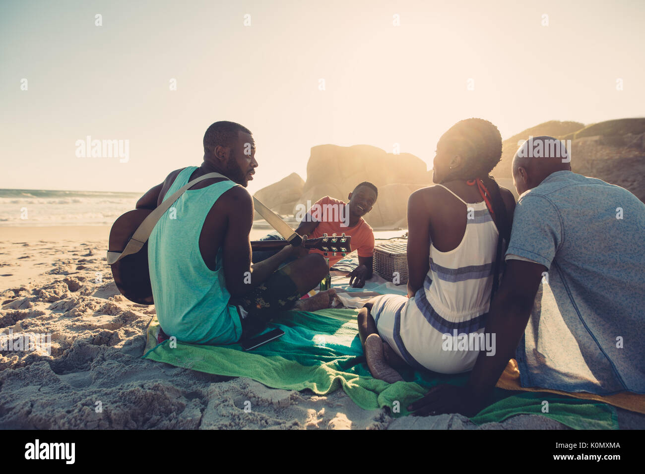 Afro american man playing guitar on the beach with friends sitting around. People on beach enjoying vacation. - Stock Image