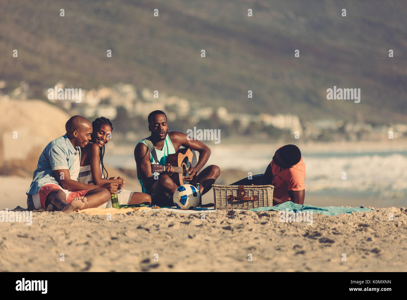Afro american young man with guitar singing a song for his friends. Group of friends on vacation relaxing at the beach. - Stock Image