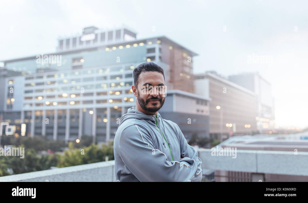 Morning runner standing on top of a building with hands folded looking at camera. Man in tracksuit with city buildings in background. - Stock Image