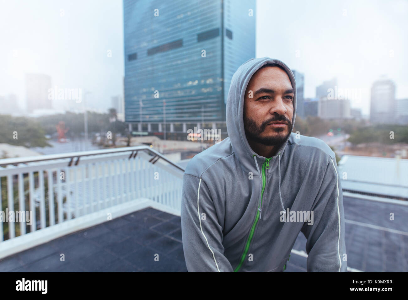 Man in hooded sweatshirt looking away. Man on top of a building against a blurred cityscape. - Stock Image