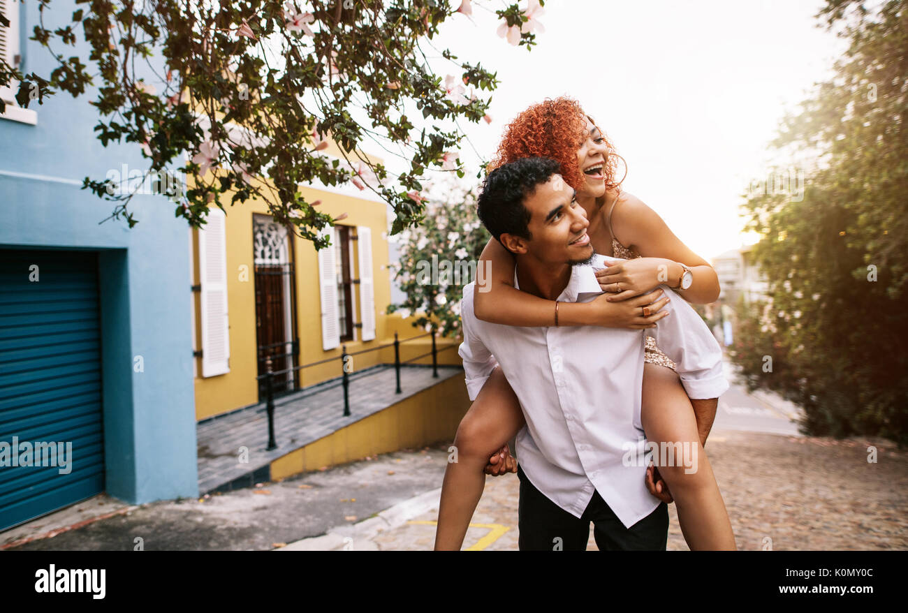 Smiling young woman riding piggy back on her partner on a lonely street . Young man carrying his partner on his back in a playful mood. - Stock Image