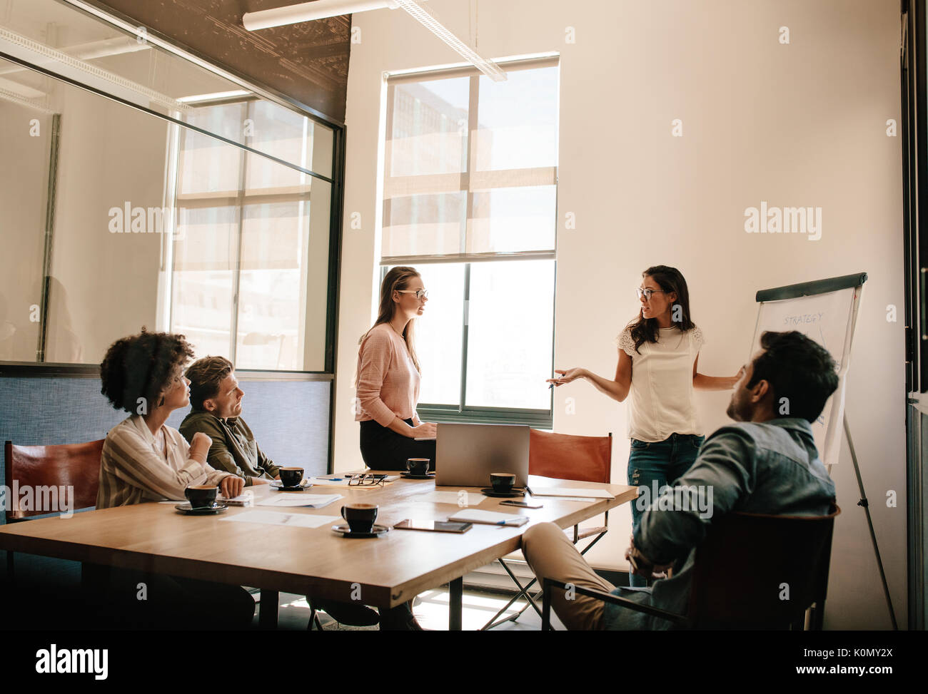 Creative business team having discussion during presentation in conference room. Businessman and woman meeting in boardroom for exploring new business - Stock Image