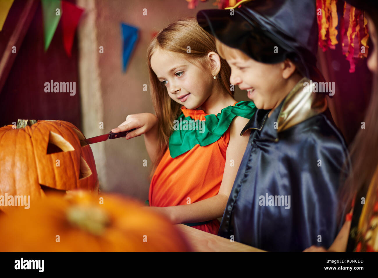 Children affectionated with carving a pumpkin - Stock Image