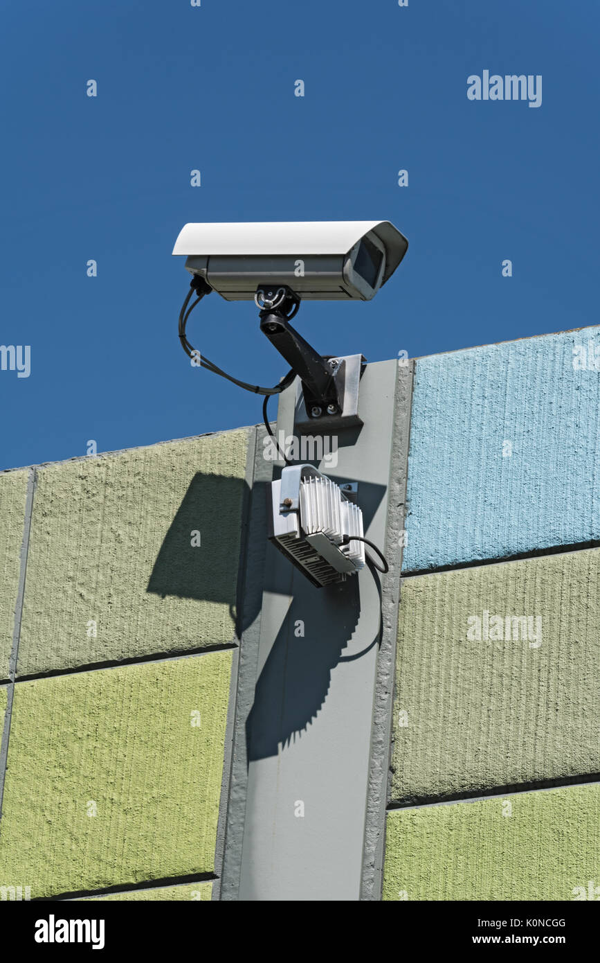 Security camera on a colorful wall with view on opposite sides - Stock Image
