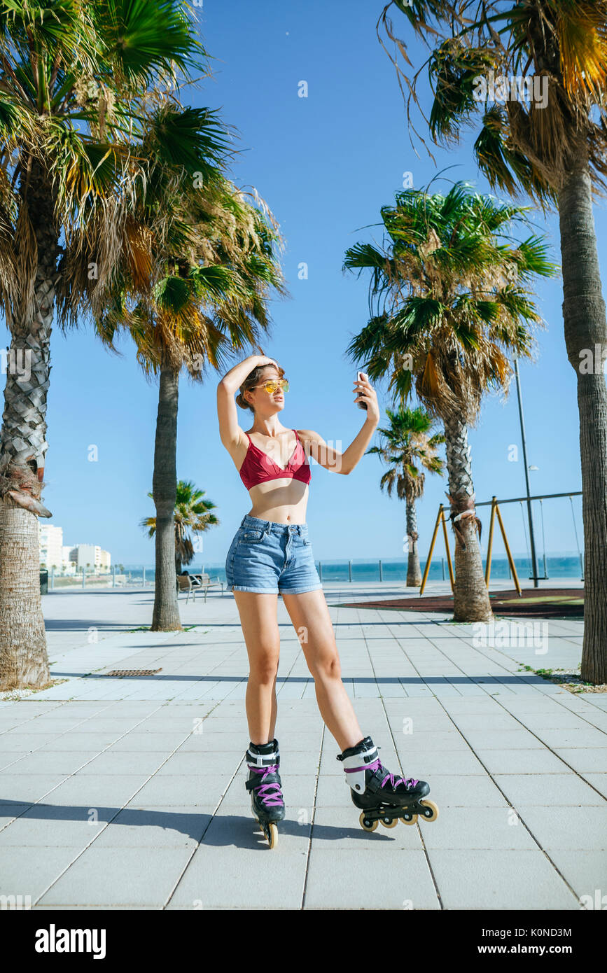 Young woman on inline skates taking a selfie on boardwalk - Stock Image