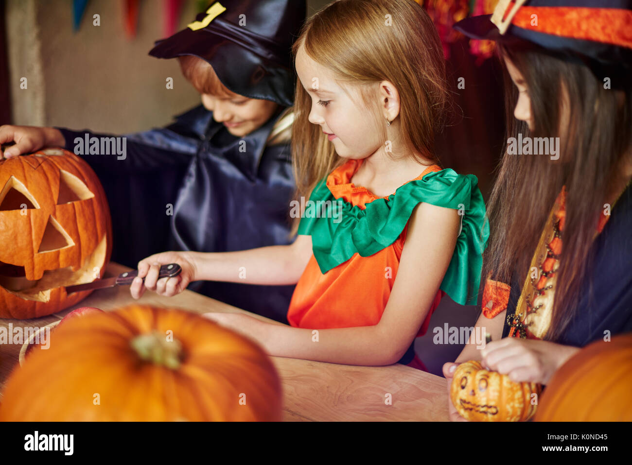 Focus children carving some shapes on the pumpkin - Stock Image