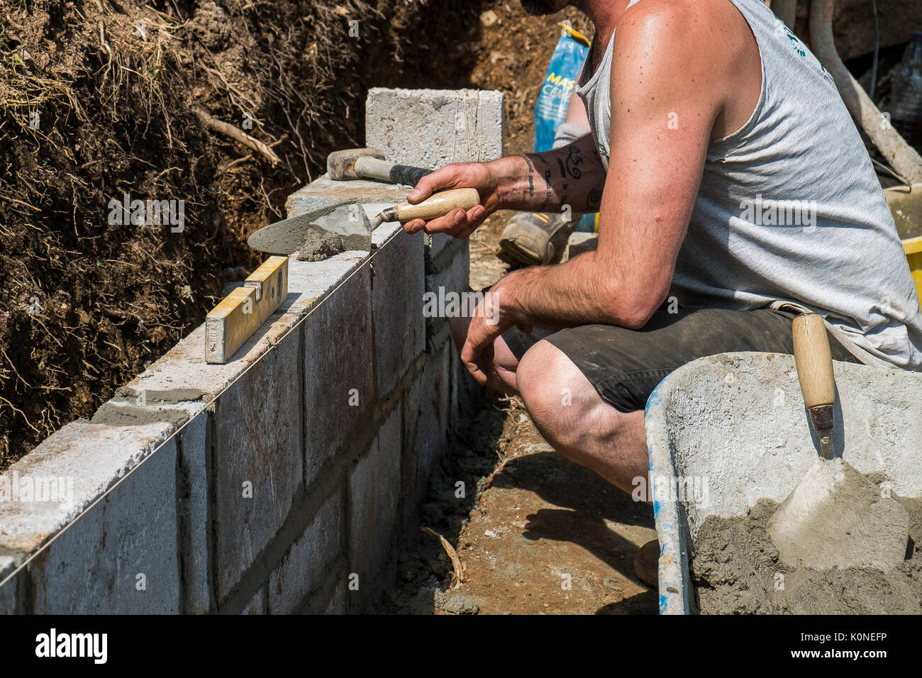 Workers building a block wall on a building site. - Stock Image
