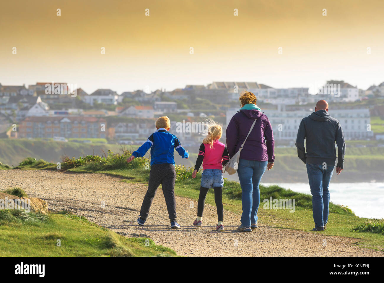 A family of holidaymakers enjoying a bracing walk in windy condition. - Stock Image