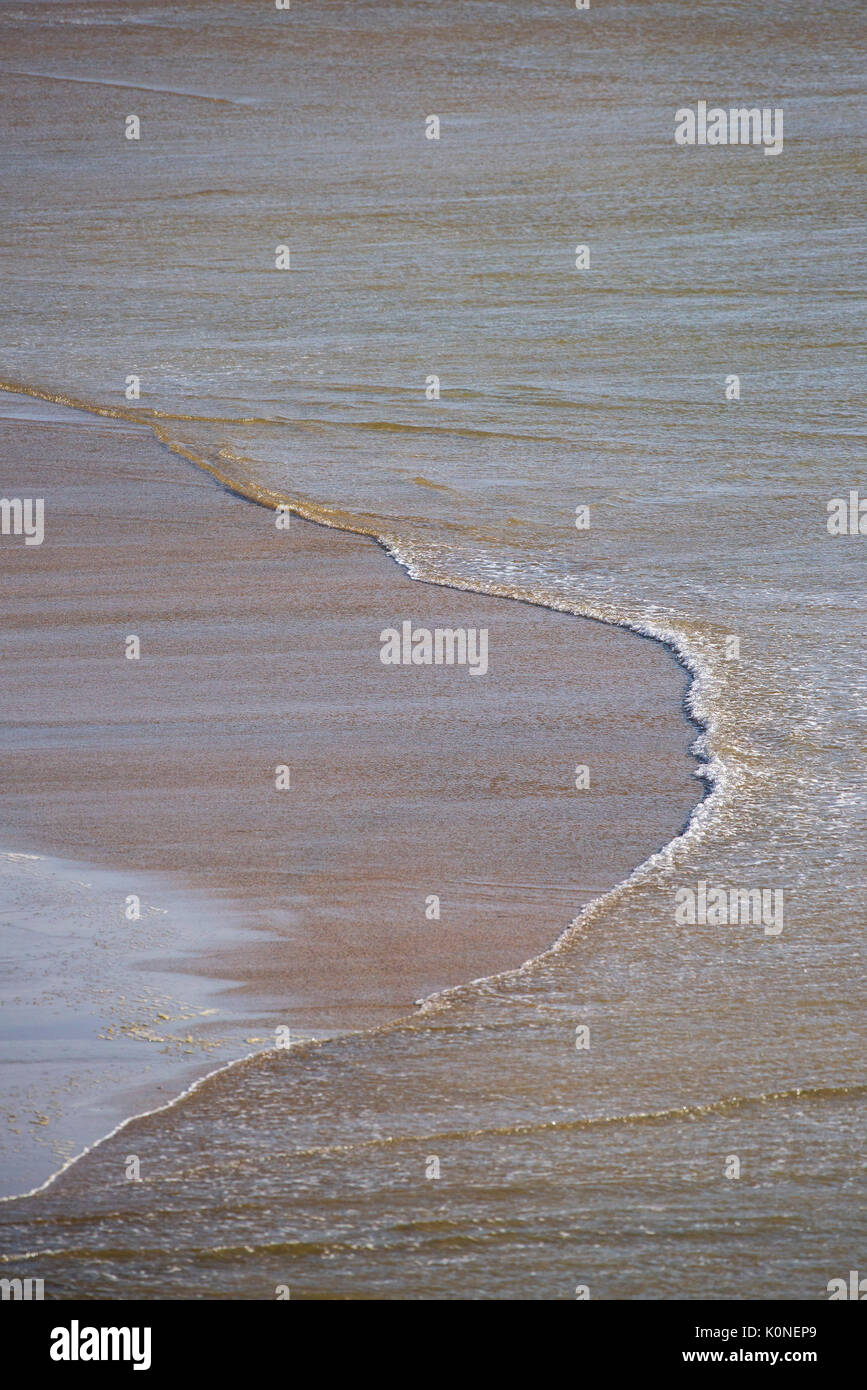 Incoming tide on a beach. - Stock Image