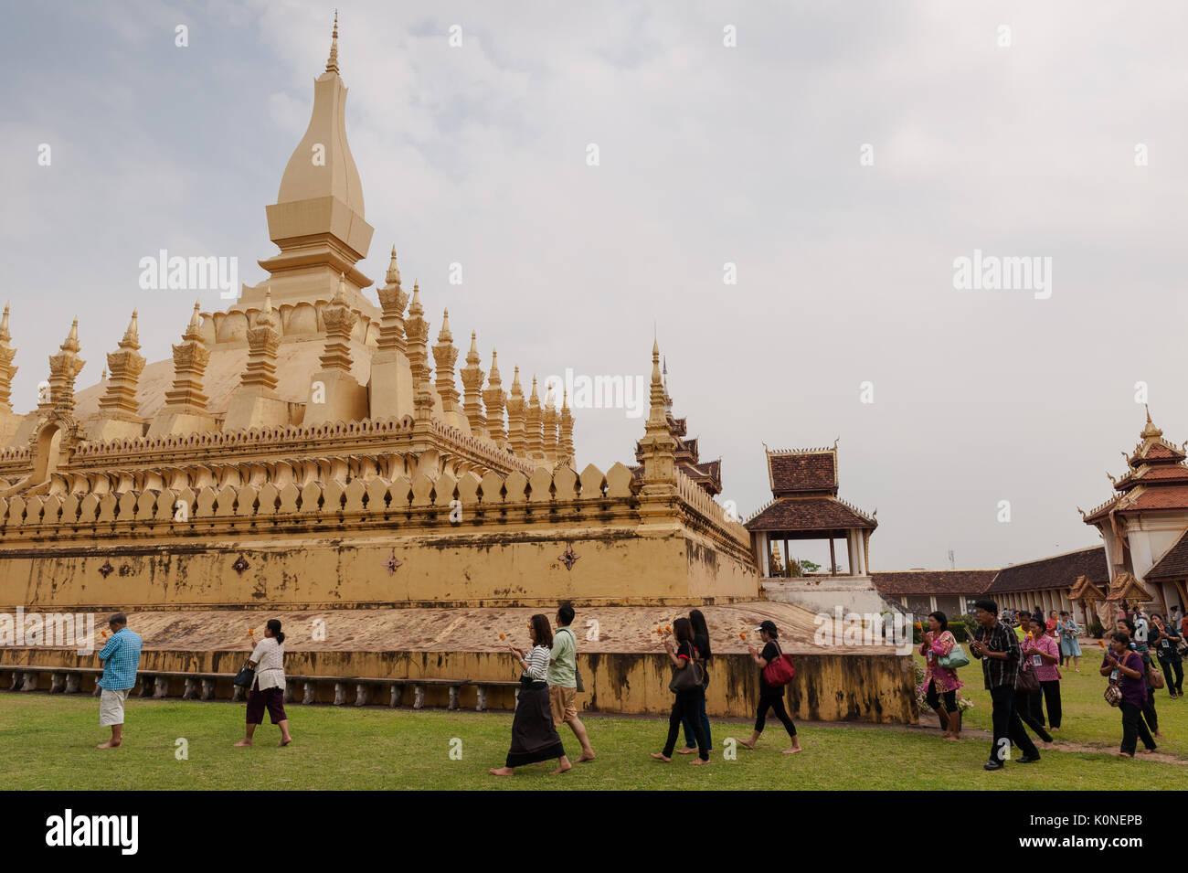 Buddhist pilgrims walk around the Great Stupa, a national symbol of Laos, Pha That Luang, Vientiane. - Stock Image