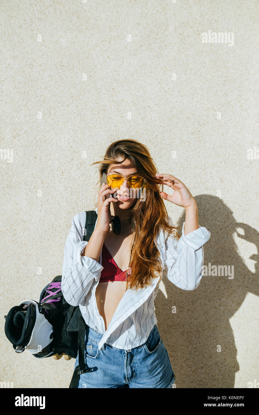 Young woman with inline skates in bag talking on cell phone - Stock Image