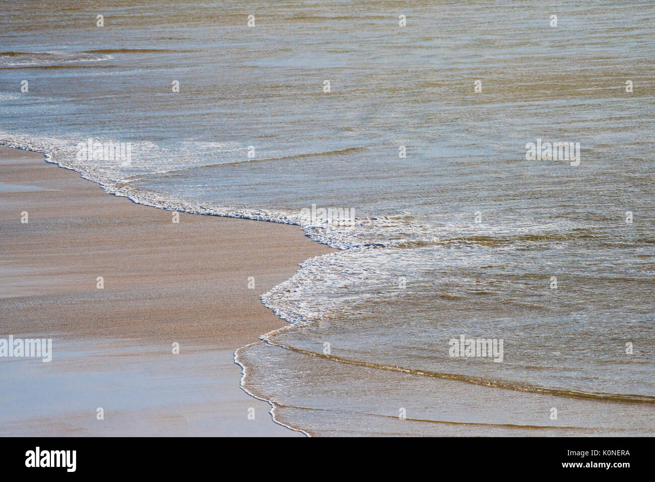 Incoming tide on a deserted beach. - Stock Image