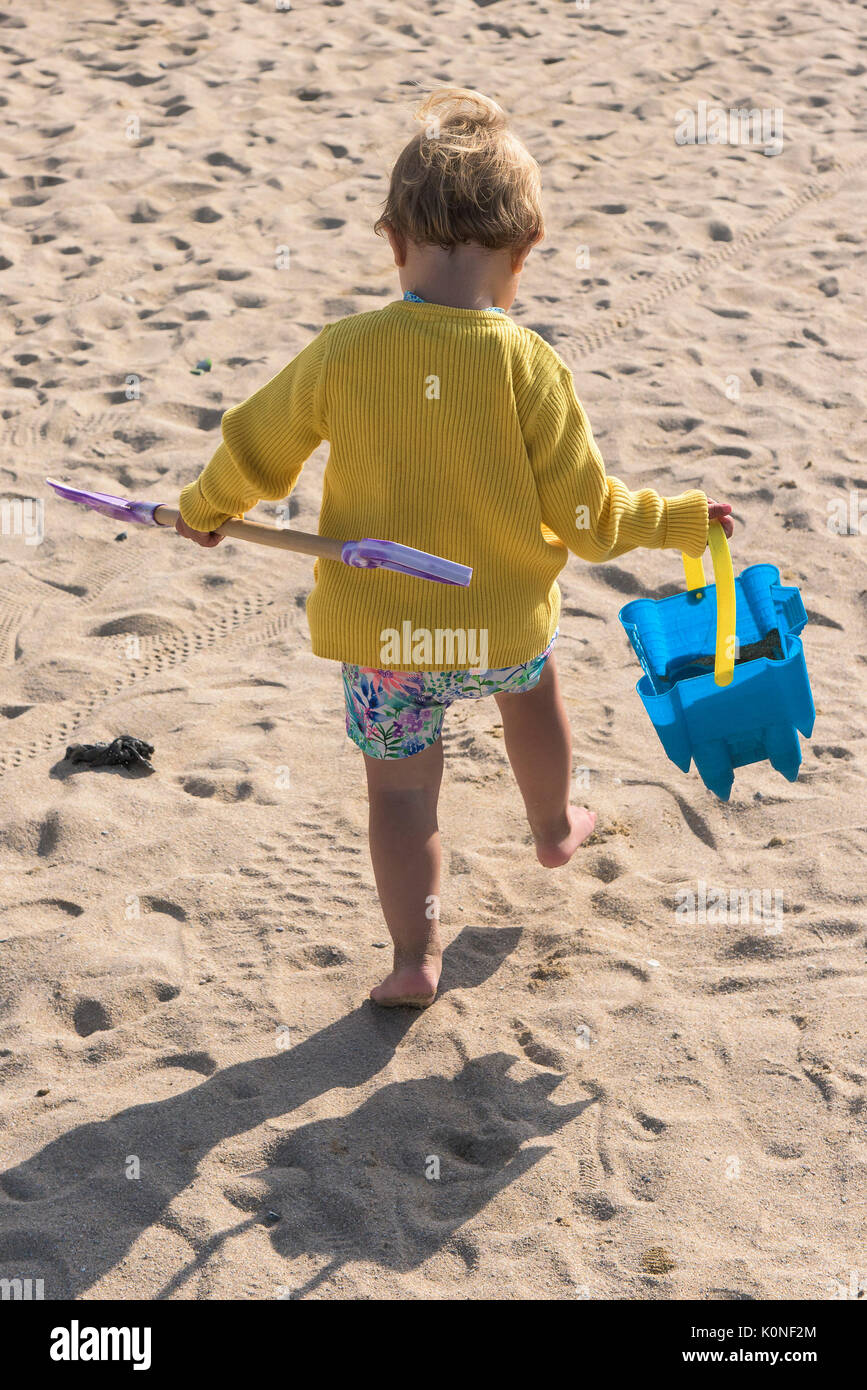 A toddler carrying her bucket and spade walking on a beach. - Stock Image