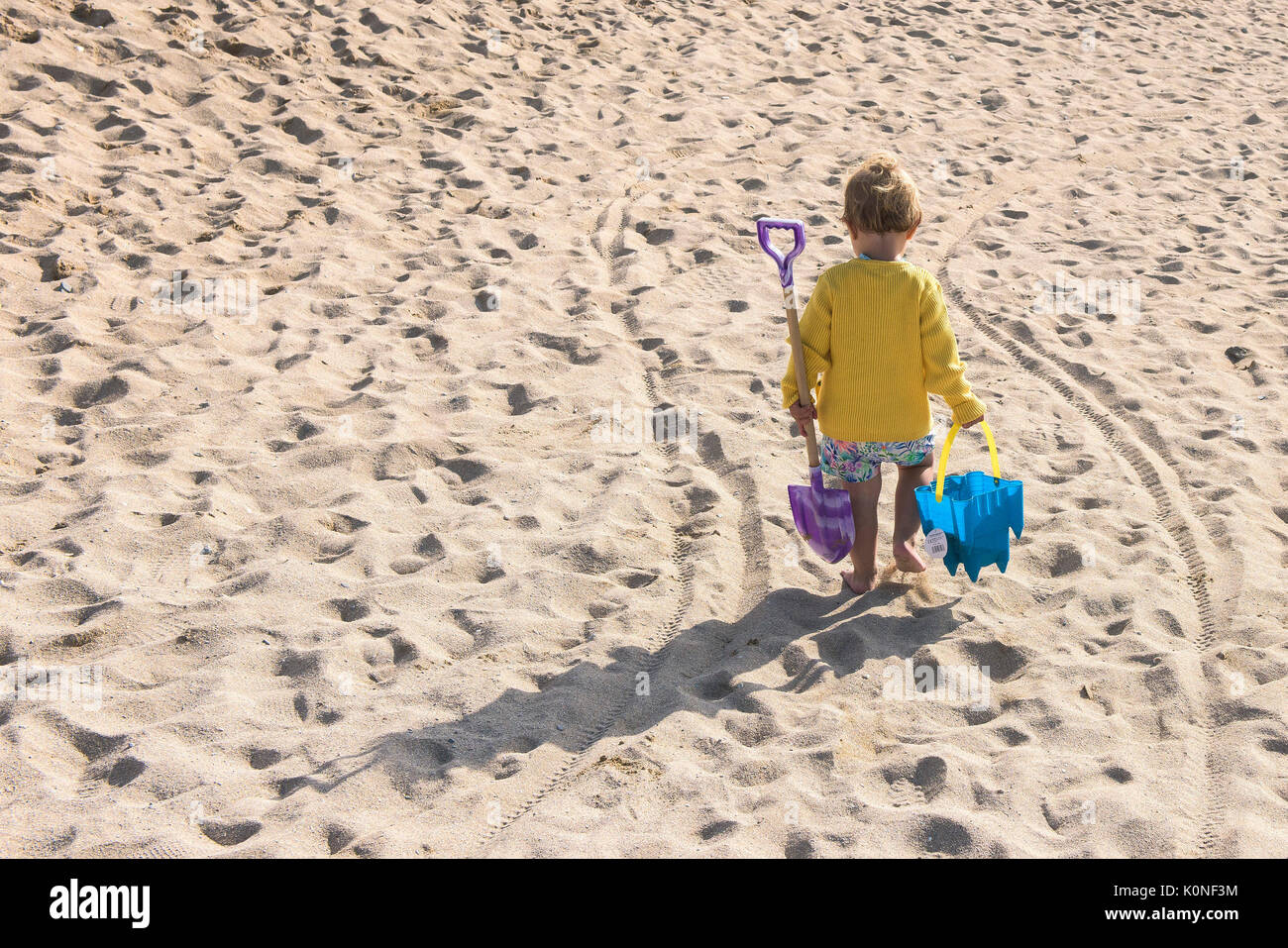 A toddler carrying her bucket and spade walking off to play on the beach. - Stock Image