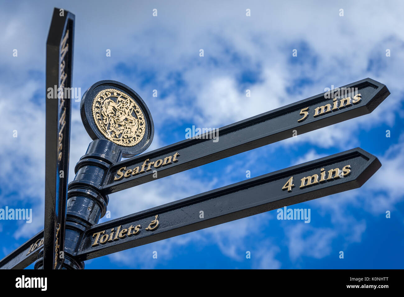 An ornate sign in the Suffolk seaside town of Southwold points the way to he seafront. - Stock Image