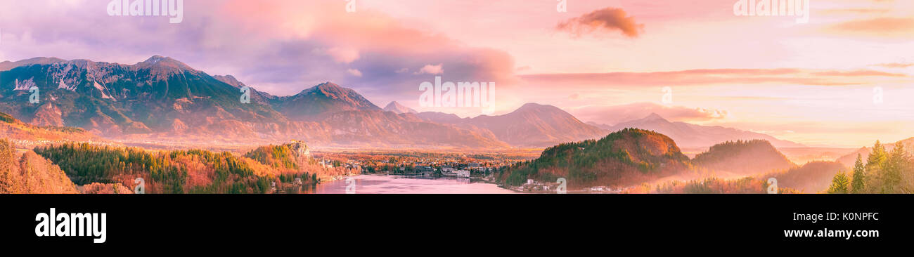Stunning and colorful panorama with the sunrise shining over the Karawanks mountains, lake Bled and its surrounding - Stock Image
