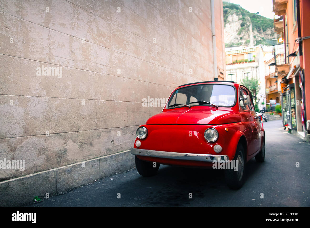 Red old well-preserved vintage Italian classic car parked in a small alley in an Italian Sicilian city with a large empty stone wall in the left side  - Stock Image