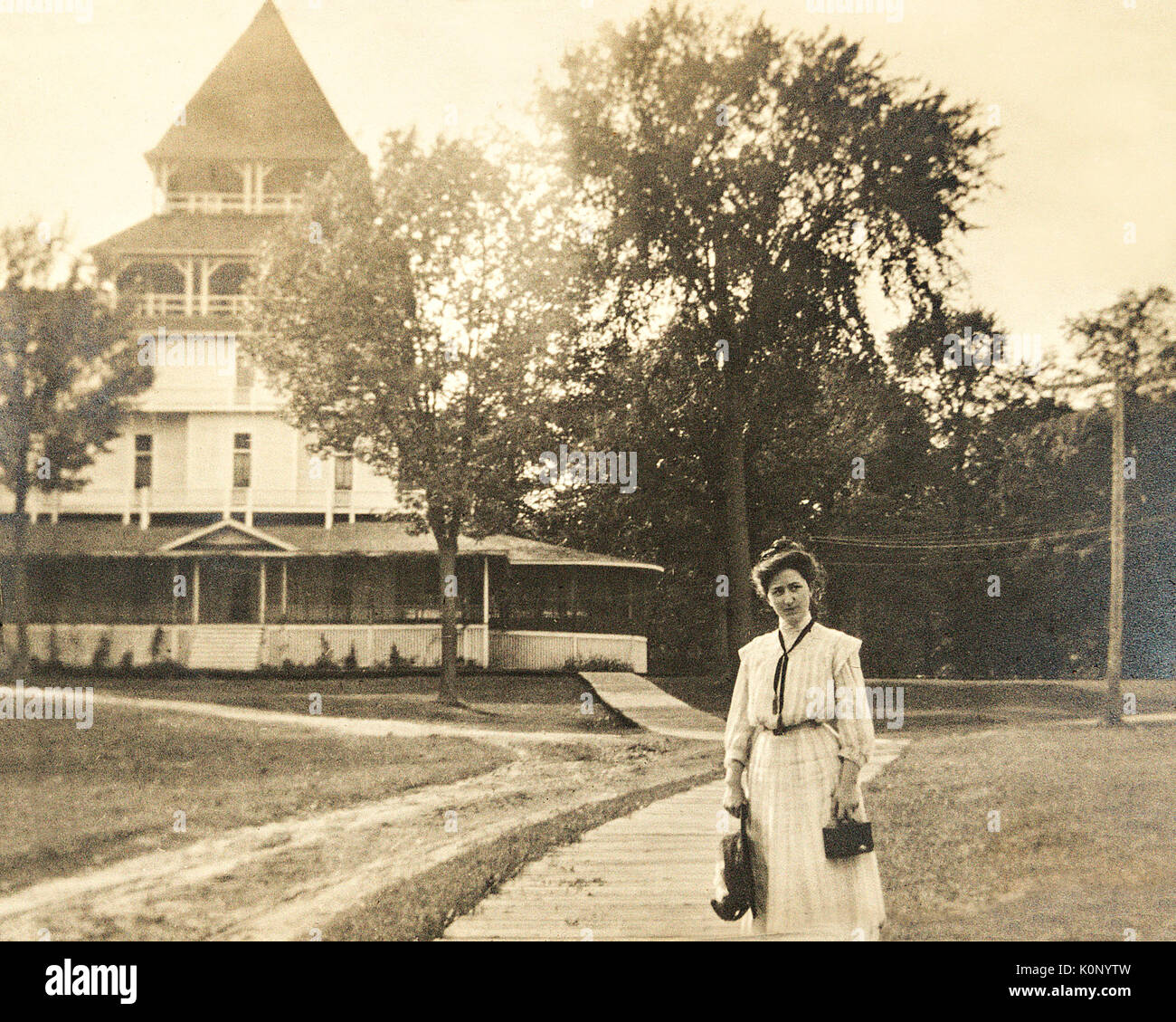 A woman standing in front of the Lake Park Hotel at Lake Minnetonka Minnesota in the year 1907 holding a camera Stock Photo