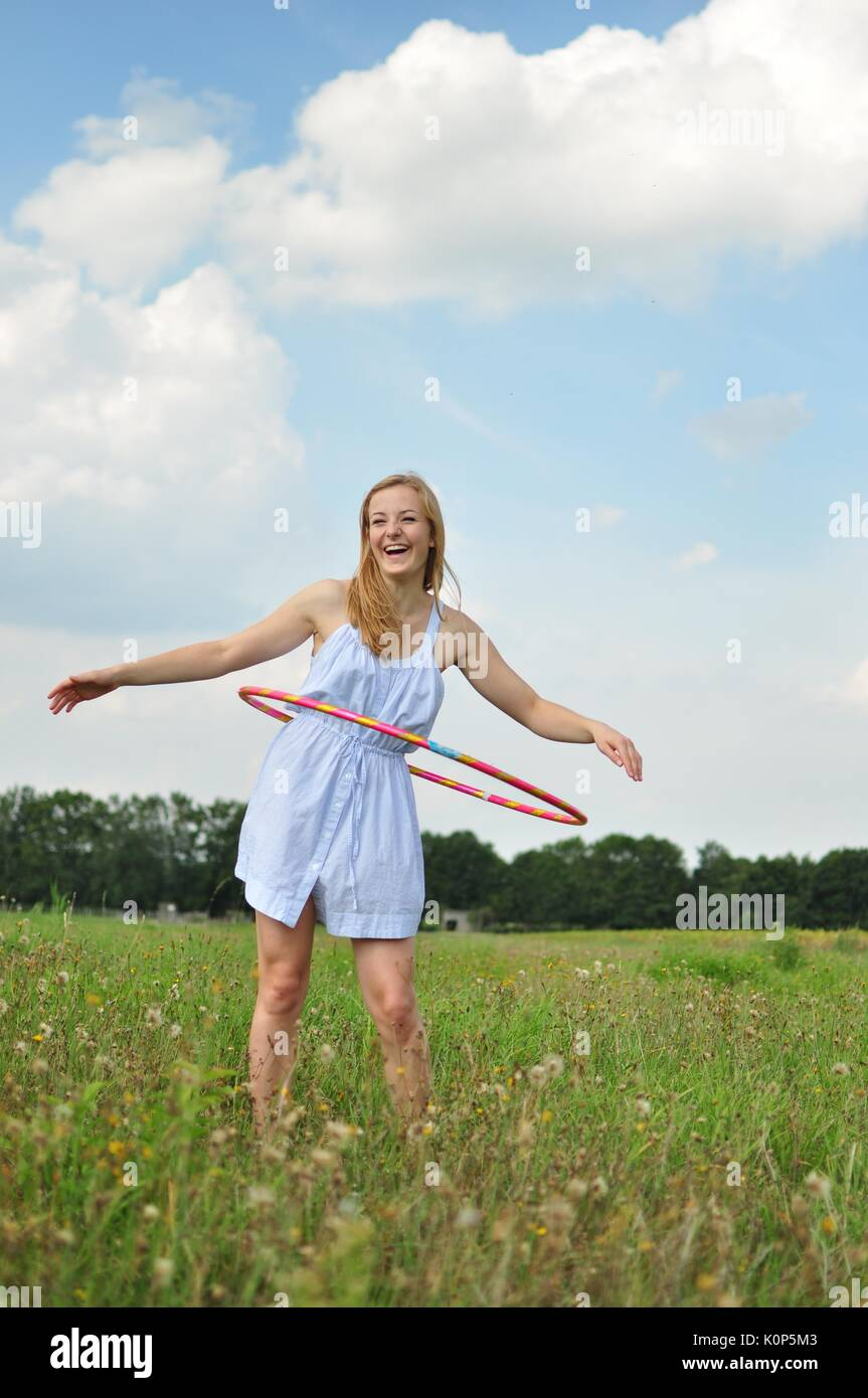 Young girl with a hula hoop on a meadow - Stock Image